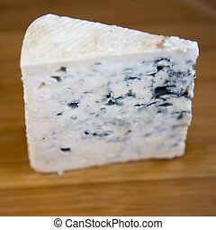Blue cheese on bamboo board, side view. Close-up.