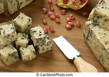 Blue cheese on wooden background.
