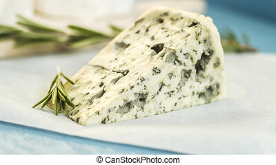 Blue cheese with rosemary on wooden board