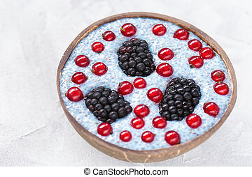 Blue chia seed pudding with blackberries and red currant berries in a bowl