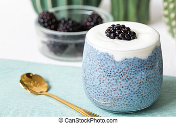 Blue chia seed pudding with blackberries in a glass