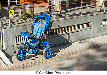 Blue children's tricycle stroller stands empty in the Parking lot near supermarket