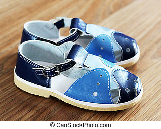 Blue child's sandals on wooden background