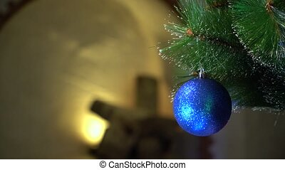 Blue Christmas ball in the flicker of colored lights.