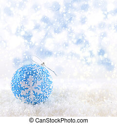 Blue Christmas ball on snowing background