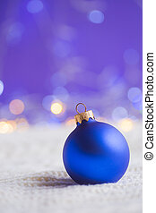Blue Christmas ball on white knitted fabric on purple background with warm bokeh