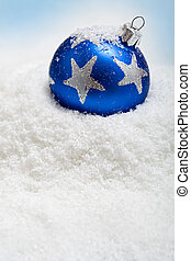 Blue christmas bauble in the snow