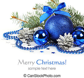Blue christmas decorations and silver pine cones over white...