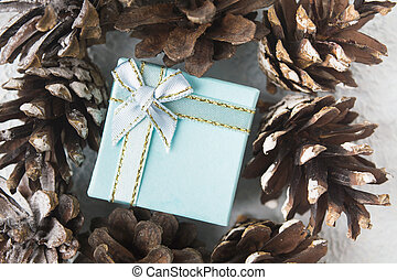 Blue Christmas gift box with pinecones, flat lay style