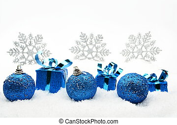 Decoration of blue christmas gifts and baubles and snowflakes on snow on white background