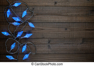 Blue christmas lights on wooden background