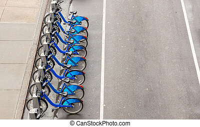 Blue city bikes parked on the street, view from above