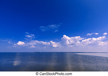 blue clear sky with white clouds over water of river on Sunny summer day