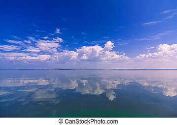 blue clear sky with white clouds reflected in calm water of sea on Sunny day