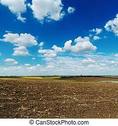 blue cloudy sky over plowed field