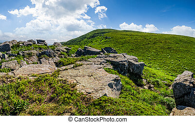 blue cloudy sky over the mountains with rocky hillside -...