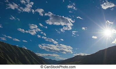 Blue cloudy sky with sunburst