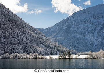 blue cloudy sky with wonderful winter landscape at lake
