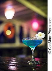 blue cocktail drink in dark bar interior