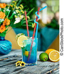 blue cocktail glass with lime and lemon