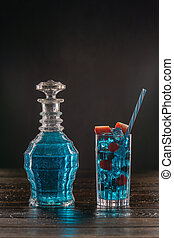 Blue cocktail in vintage decanter and in a glass on wooden table