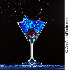 blue cocktail splashing on dark background