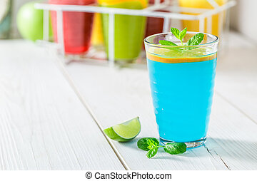 Blue cocktail with fresh fruits on white table