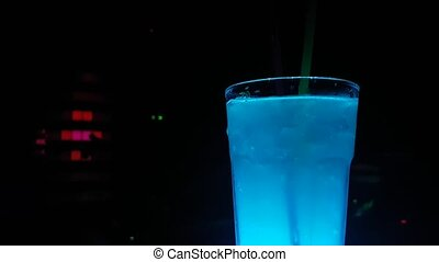 Blue Cocktail With Moving Straw and Disco Club Lights in Background