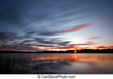 Blue cold sunrise over lake - Brilliantly colorful sky at...