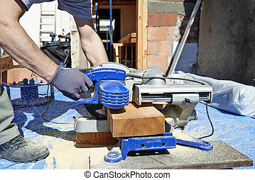 Blue collar carpenter using electric saw