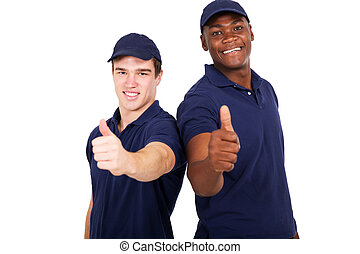 blue collar co-workers giving thumbs up - two blue collar...