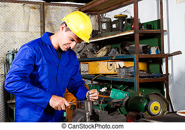 blue collar factory worker working in workshop