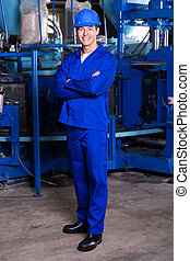 blue collar industrial worker with arms crossed in factory