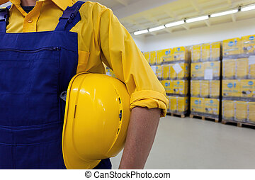 Closeup of a blue collar worker holding hard hat