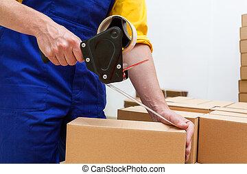 Blue collar worker with tape gun - Closeup of a worker hands...