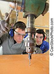 blue collars using drillhead in workshop
