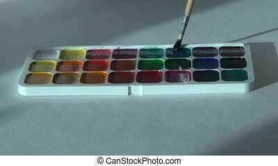 blue color. Artist works with brush and watercolor paints....