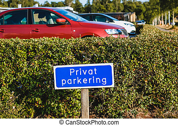 Blue colored sign with information in Swedish PRIVAT PARKERING at the entrance of car park