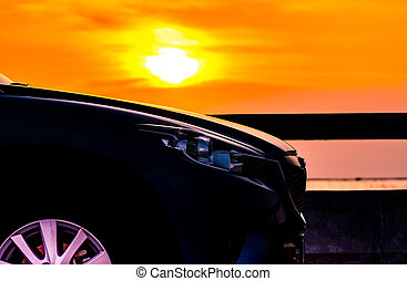 Blue compact SUV car with sport and luxury design parked on concrete road by the sea at sunset. Electric car technology and business. Hybrid auto and automotive industry. Tropical road trip travel.
