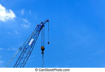 Construction crane on blue sky background in progress at Construction Site.
