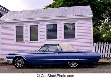 Blue convertible thunderbird car over pink wooen house