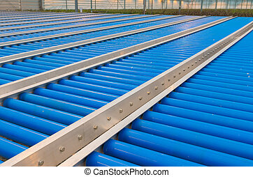 conveyor belt - blue conveyor belt rollers in a greenhouse