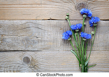 Blue cornflowers on wooden background