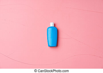 Blue cosmetic bottle on textured pink background