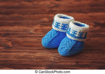Blue crochet baby booties on wooden background, copyspace, vintage toned