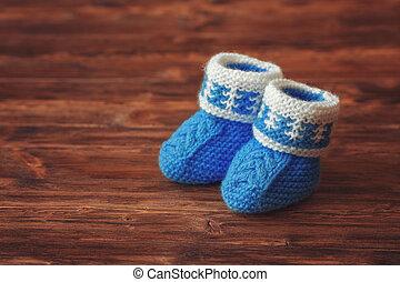 Blue crochet baby booties on wooden background, copyspace, vintage toned