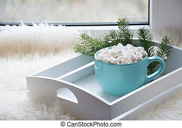 Blue cup of hot chocolate with marshmallow on windowsill. Weekend concept. Home style. Christmas time.