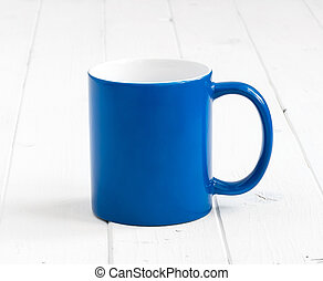 blue cup with white inside on wooden table