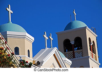 Blue cupolas of Greek orthodox church with red hibiscus tree