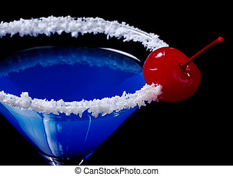 Blue Curacao with coco flakes on the glass rim and garnished with a red maraschino cherry photographed on black (Selective Focus, Focus on the cherry)